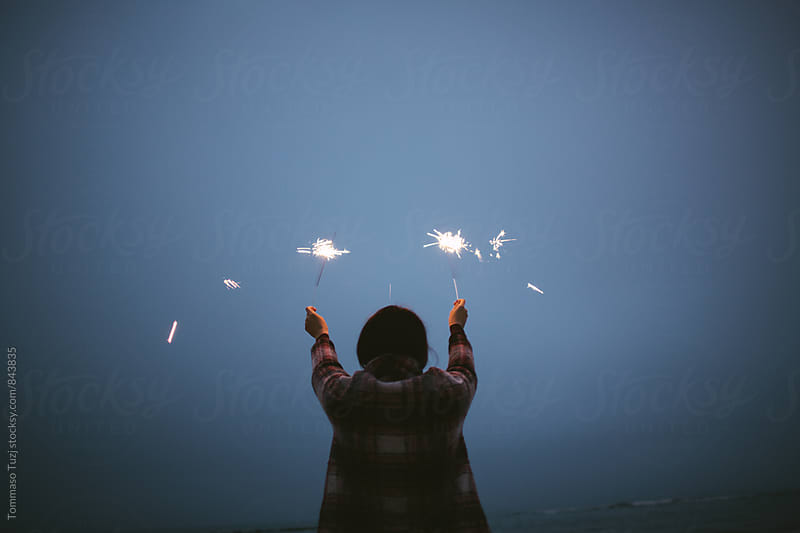 Girl on the beach holding sparkle sticks by Tommaso Tuzj for Stocksy United