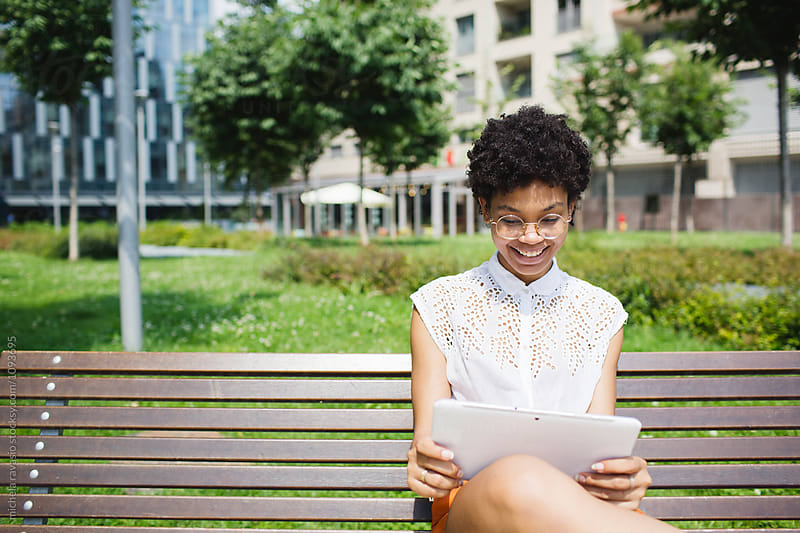 Smiling young woman using her digital tablet on the bench by michela ravasio for Stocksy United