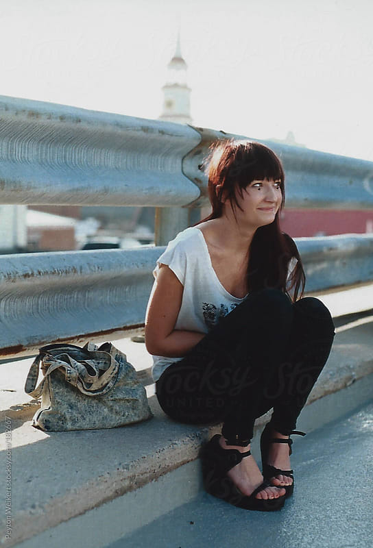 Fashionable young woman sitting and smiling near guardrail  by Peyton Weikert for Stocksy United