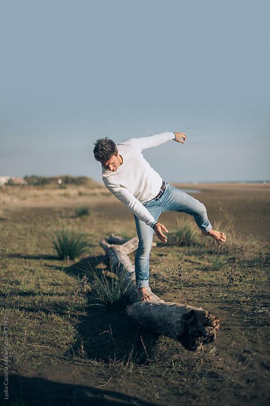 Boy balancing on a log in the beach by Lydia Cazorla for Stocksy United