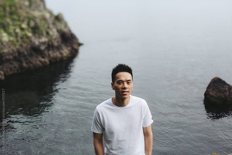 Portrait of young asian man standing ansd smiling near ocean water by Rob and Julia Campbell for Stocksy United
