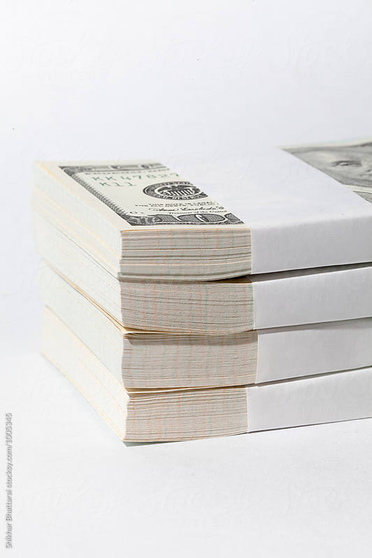 Stack of dollar bills on white. by Shikhar Bhattarai for Stocksy United