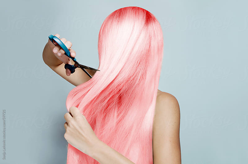 woman cutting her long pink hair by Sonja Lekovic for Stocksy United