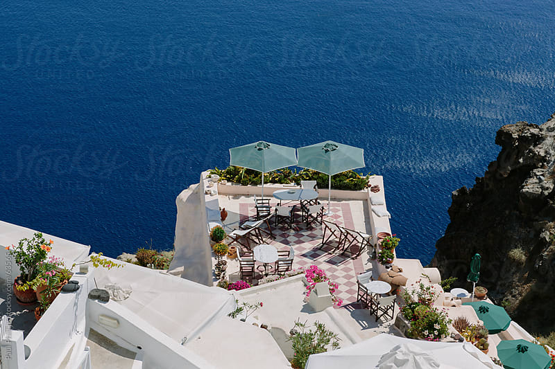 Balcony with parasols over looking the caldera of Santorini by Paul Phillips for Stocksy United