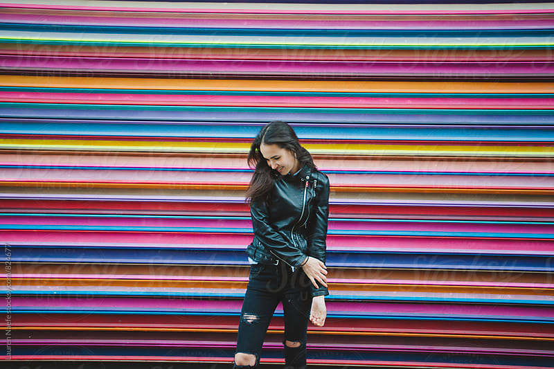 Young urban woman and rainbow wall by Lauren Naefe for Stocksy United