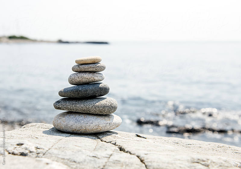 Stack of beach stones overlooking the ocean by Cara Dolan for Stocksy United