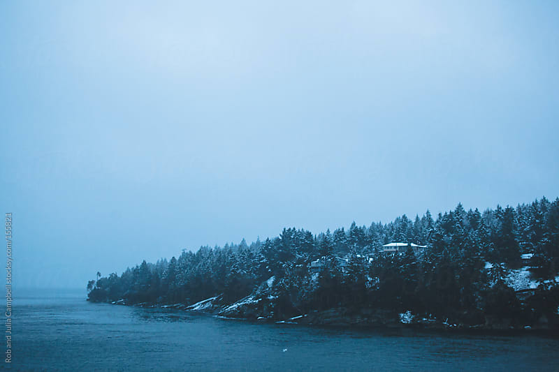 West coast view of snowy trees from cold morning ferry boat sail by Rob and Julia Campbell for Stocksy United