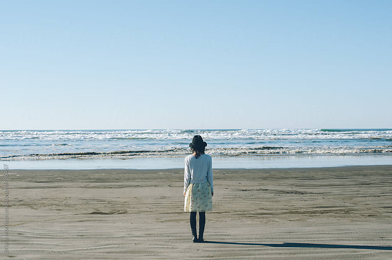 Young Woman Standing Alone on the Beach by Briana Morrison for Stocksy United