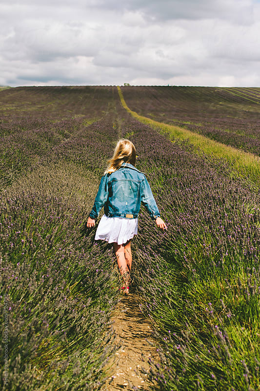 Girl walking through a field of lavender by Helen Rushbrook for Stocksy United