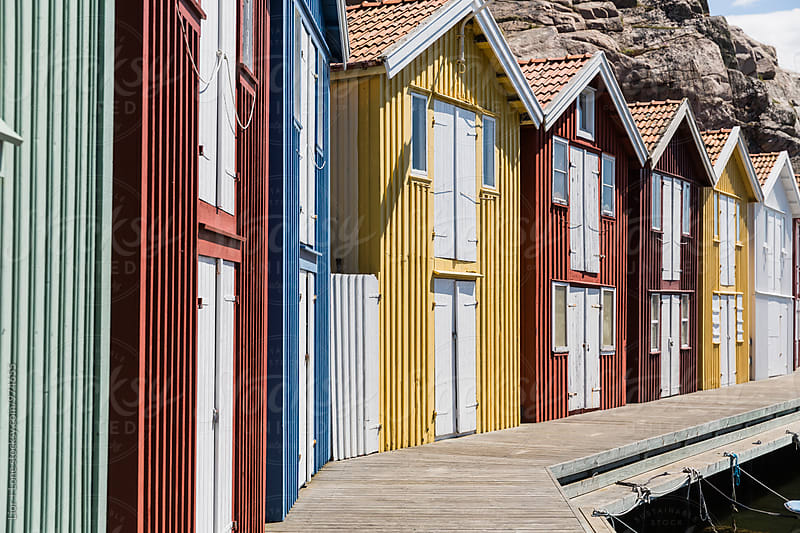 Identical Swedish wooden fishermen huts in a harbour by Lior + Lone for Stocksy United