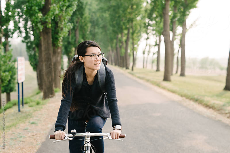 Young girl riding bicycle on a road by MaaHoo Studio for Stocksy United
