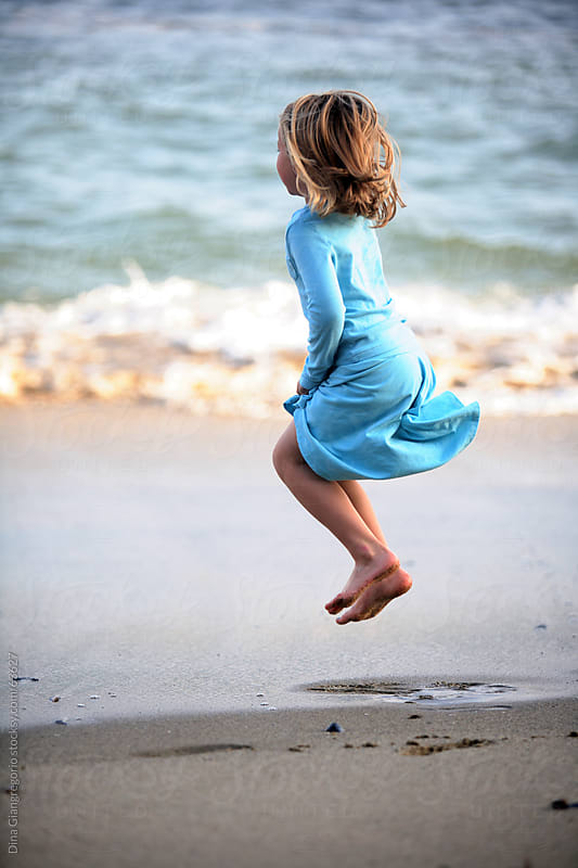 Girl jumping on the beach wearing blue dress  by Dina Giangregorio for Stocksy United