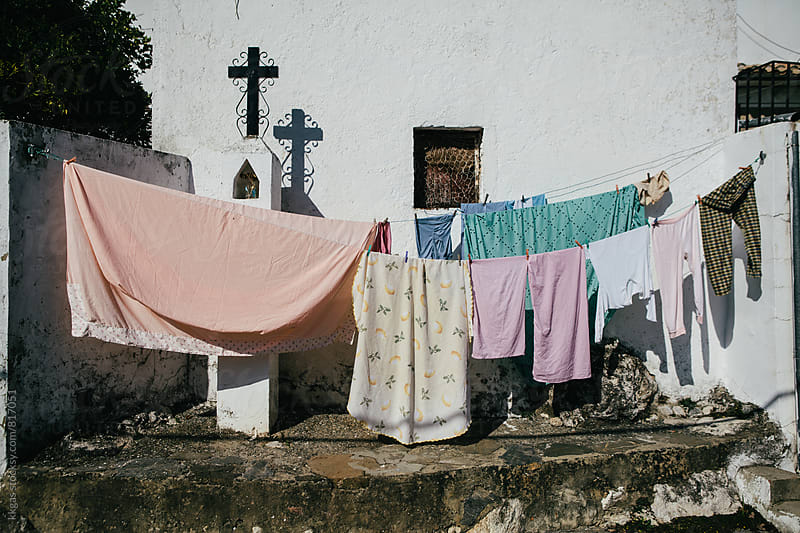 Laundry hanging out to dry surrounding a crucifix  by kkgas for Stocksy United