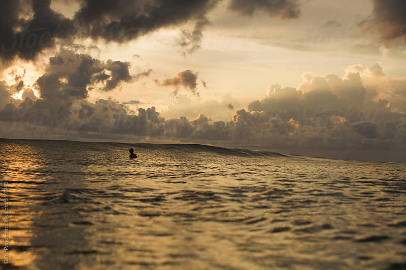 A surfer sits in the lineup alone as the sun sets and turns the water golden by Gary Parker for Stocksy United