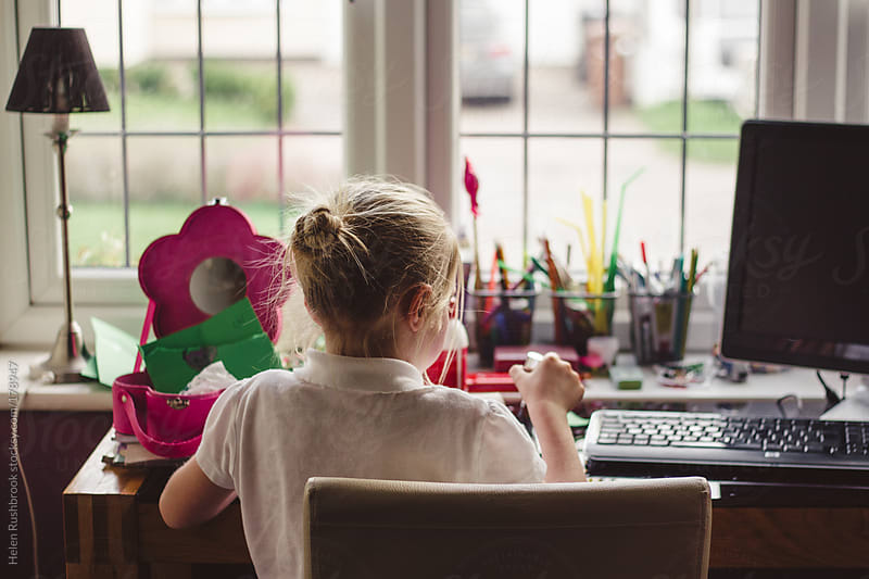 A little girl sitting at her desk by Helen Rushbrook for Stocksy United