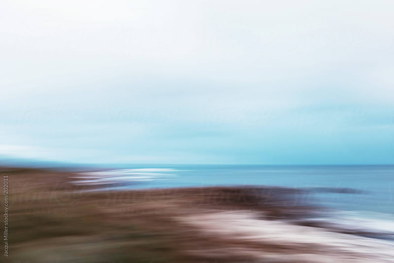 Softly blurred view of a rocky coastline by Jacqui Miller for Stocksy United