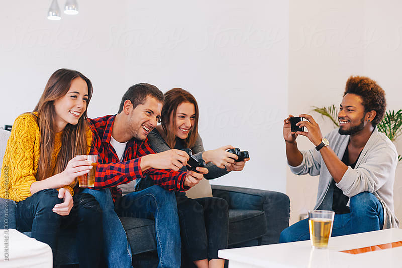 Young man taking a photo of his friends while they playing video games at home. by BONNINSTUDIO for Stocksy United