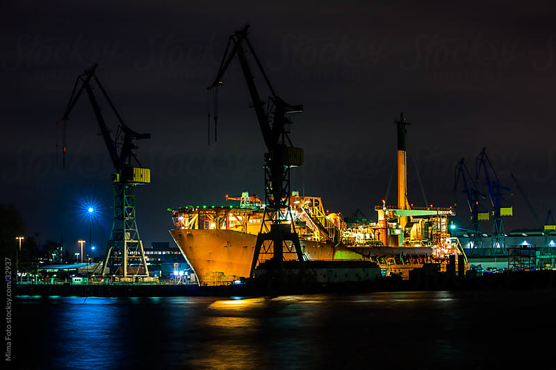 Commercial freight ship in Hamburg harbor at night by Mima Foto for Stocksy United