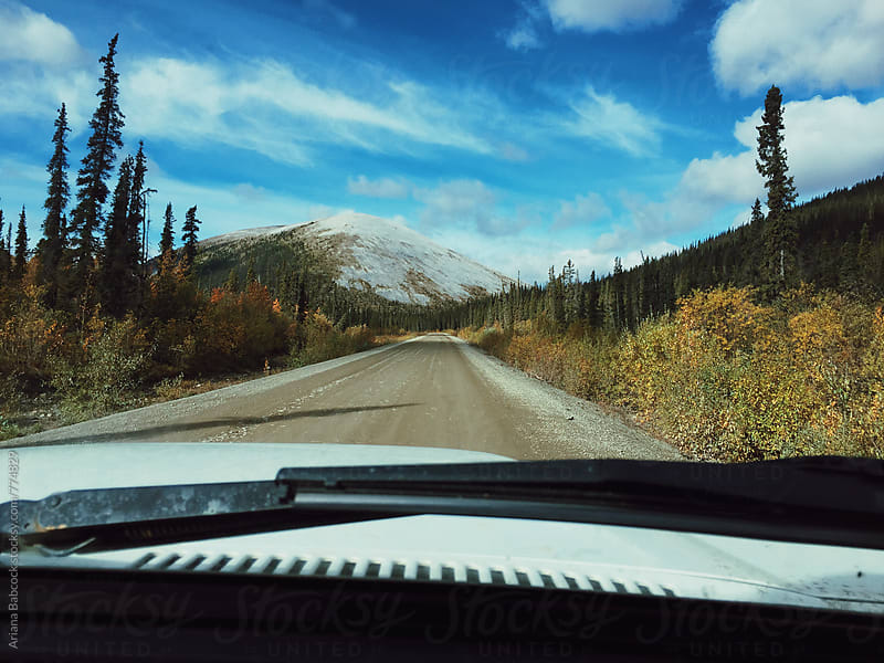 Driving a long road by Ariana Babcock for Stocksy United