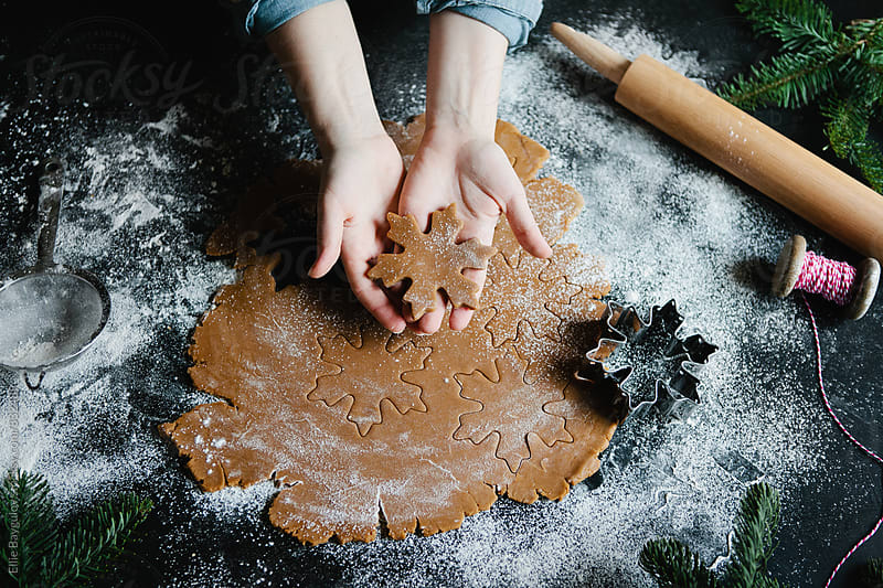 Woman making holiday cookies by Ellie Baygulov for Stocksy United