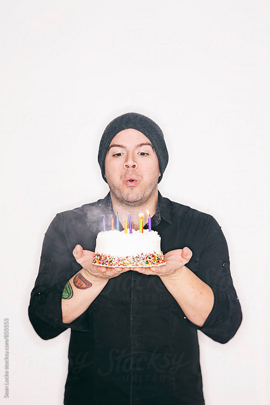Celebrate: Man Blows Out Birthday Candles by Sean Locke for Stocksy United