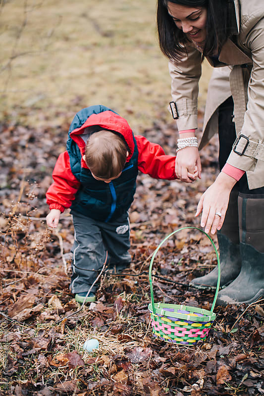a toddler finding easter eggs outside with his mom by Sarah Lalone for Stocksy United