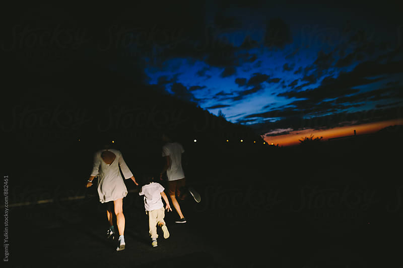 Family running away in the headlights by Evgenij Yulkin for Stocksy United