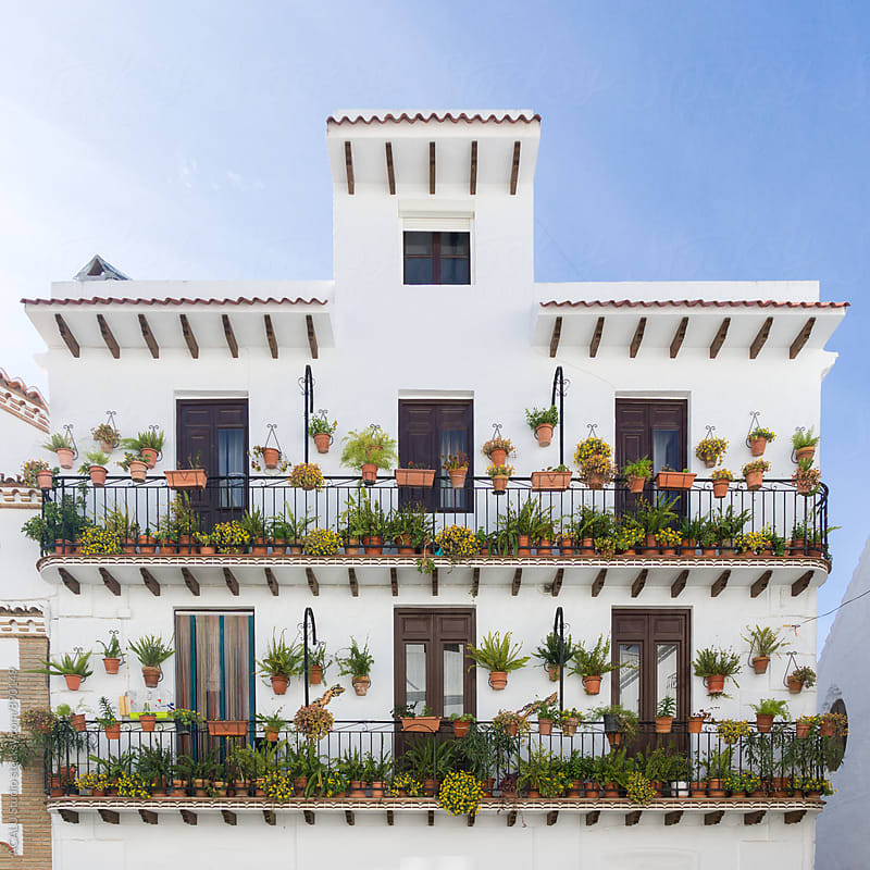 Andalusian building facade with pots on balconies by ACALU Studio for Stocksy United