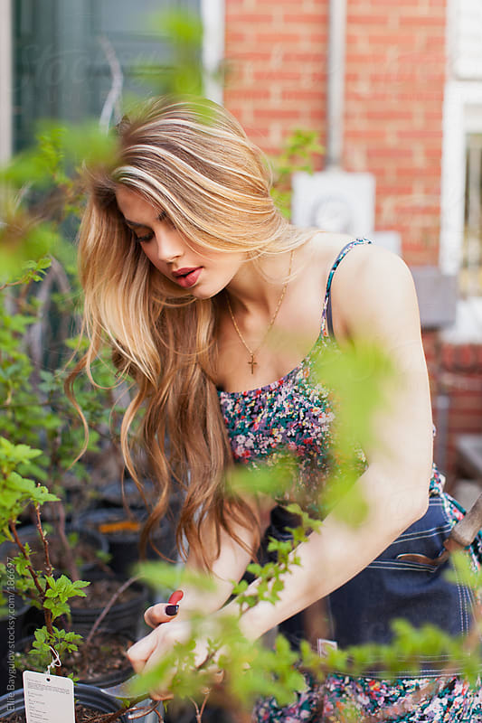 Beautiful young woman working in a garden by Ellie Baygulov for Stocksy United