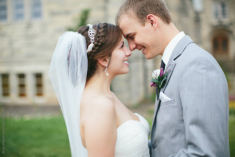 Bride and groom outside church by Brian Powell for Stocksy United