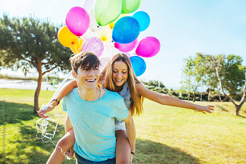 Teenage couple having fun in a park on a sunny day. by BONNINSTUDIO for Stocksy United
