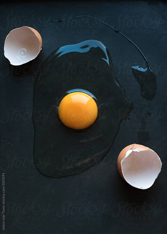 Fresh raw egg on a dark background by Jelena Jojic Tomic for Stocksy United