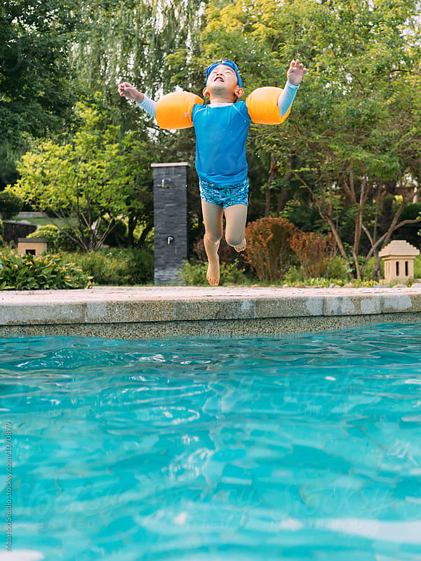 Boy jumping into swimming pool by Maa Hoo for Stocksy United