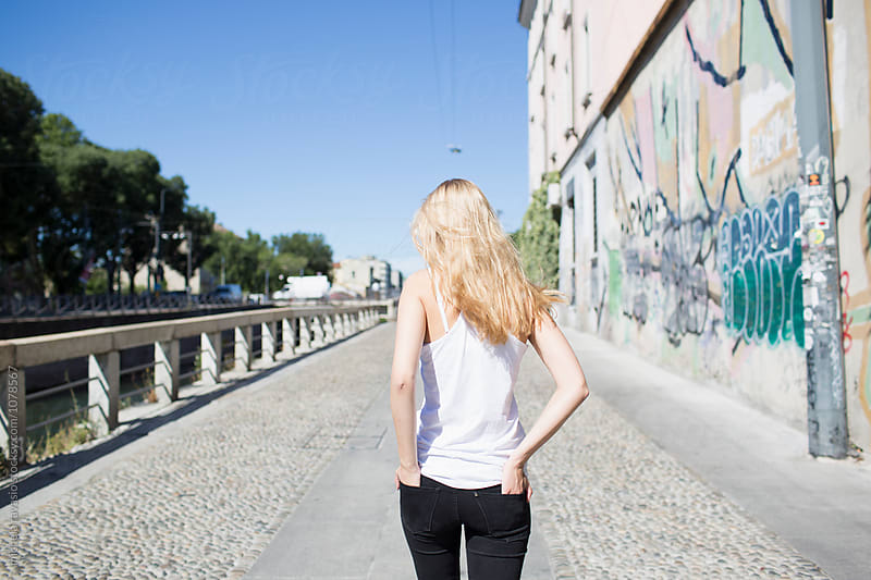 Blonde girl walking down a street alone by michela ravasio for Stocksy United
