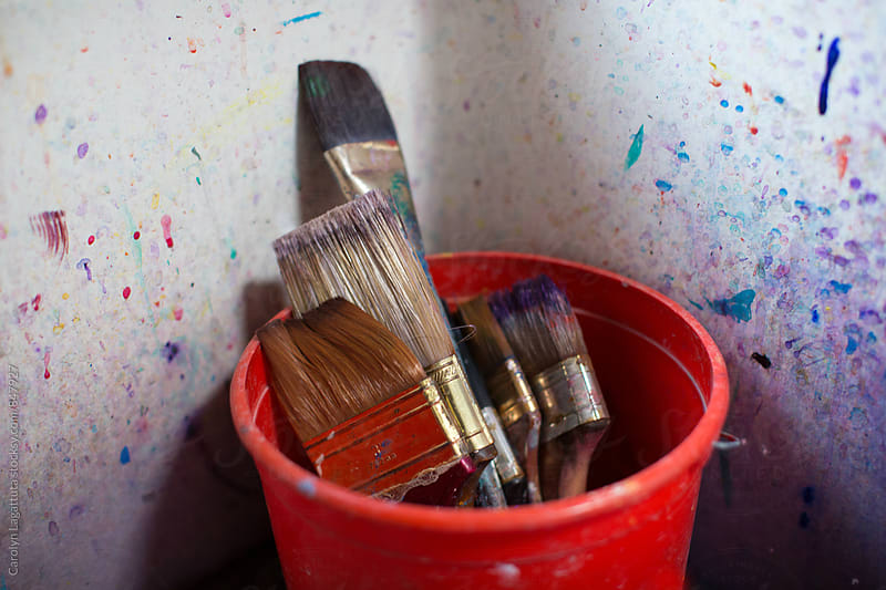 Many paint brushed in a red bucket inside a paint splattered sink by Carolyn Lagattuta for Stocksy United