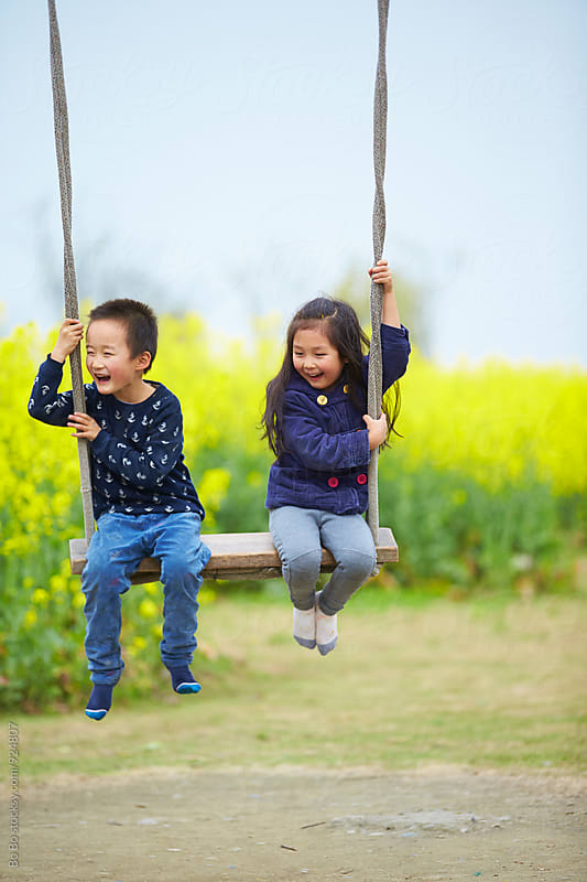 happy kids on swing by cuiyan Liu for Stocksy United