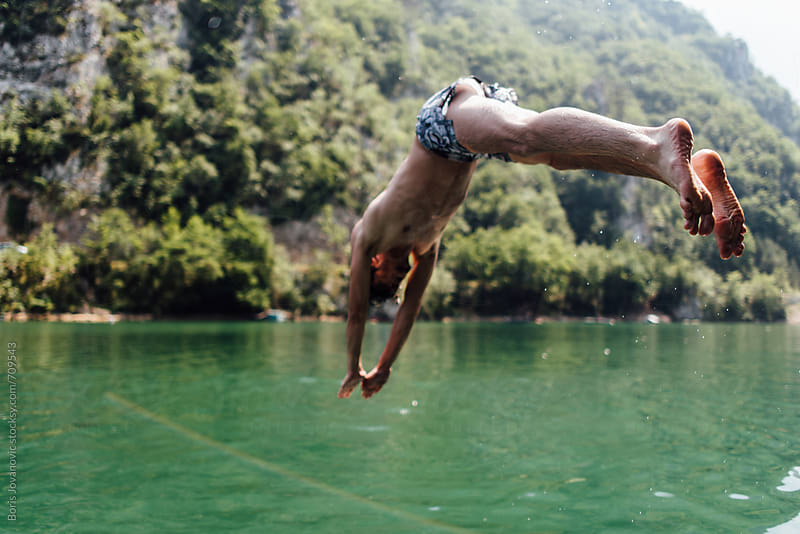 Man jumping in to the lake by Boris Jovanovic for Stocksy United
