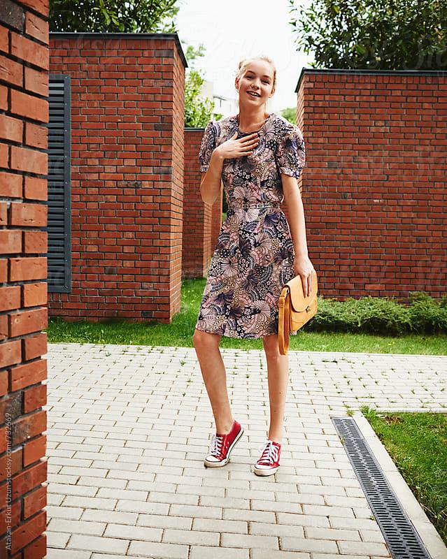 Blonde girl posing against brick walls by Atakan-Erkut Uzun for Stocksy United