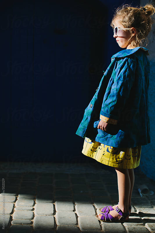a girl with sunglasses and a blue jacket stands in profile in a ray of light by Rebecca Zeller for Stocksy United