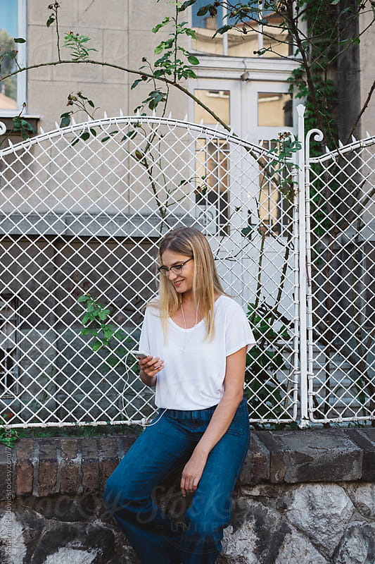 Pretty Blond Woman Sitting on the Fence by Katarina Radovic for Stocksy United