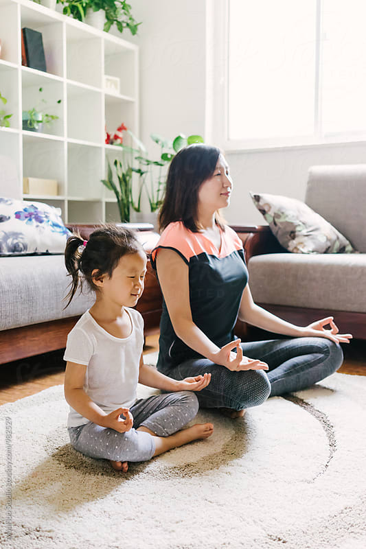 Adorable little girl doing yoga with her mother by MaaHoo Studio for Stocksy United