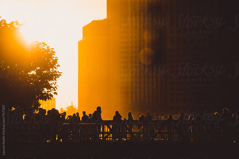People watching NYC skyline at sunset by Lauren Naefe for Stocksy United