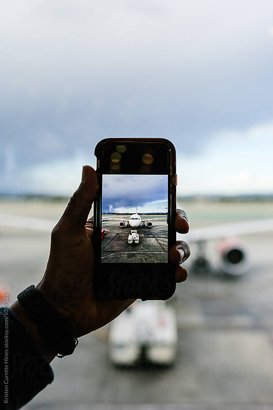 A man taking a photo of the airplane with his mobile phone.  by Kristen Curette Hines for Stocksy United