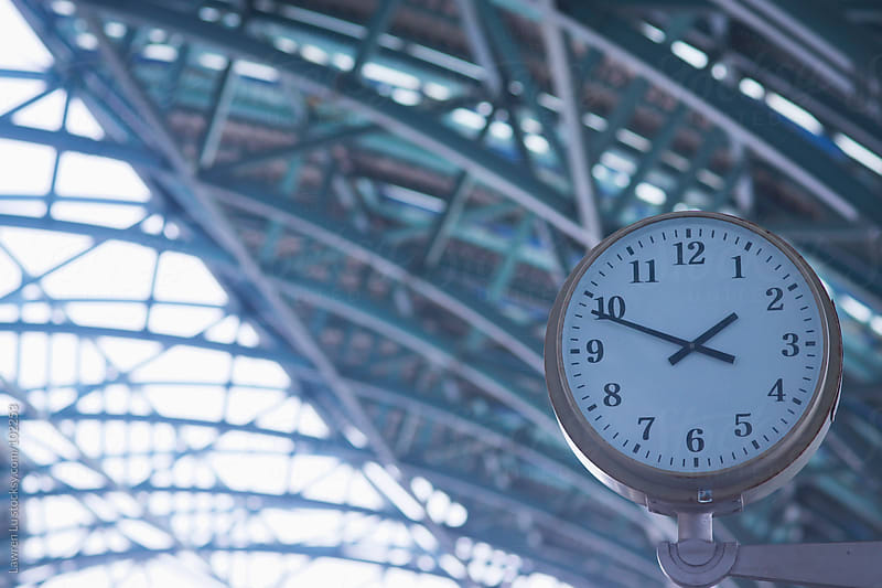 Clock hanging in modern railway station  by Lawren Lu for Stocksy United