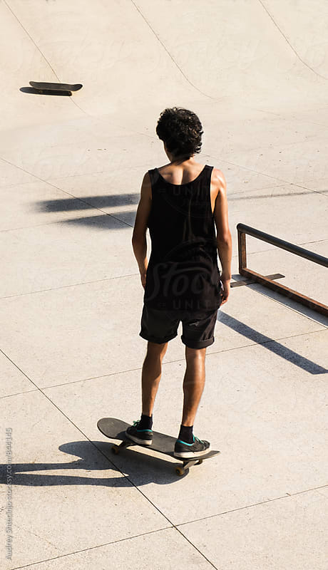 Skateboarder standing alone in skate park/look from above. by Marko Milanovic for Stocksy United