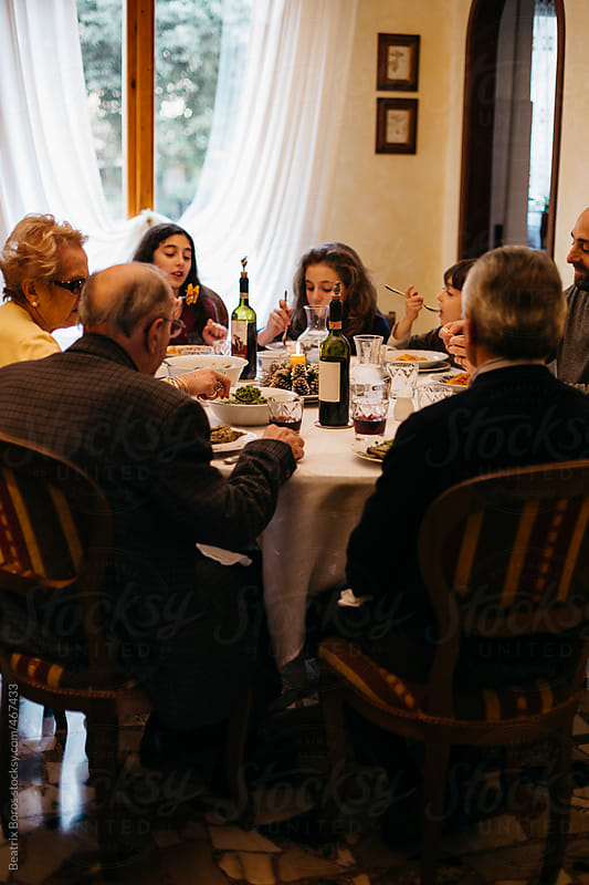 Three generations of an Italian family eating Christmas lunch together by Beatrix Boros for Stocksy United