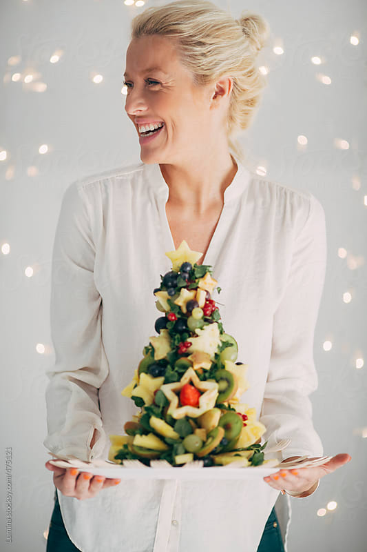 Happy Blonde Woman Holding a Christmas Tree Made of Fruit by Lumina for Stocksy United