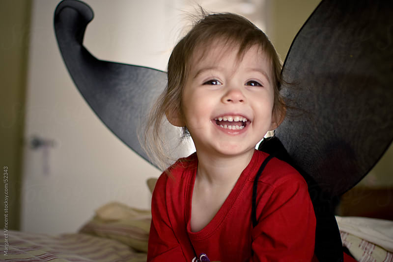 little girl plays happily while wearing wings by Margaret Vincent for Stocksy United