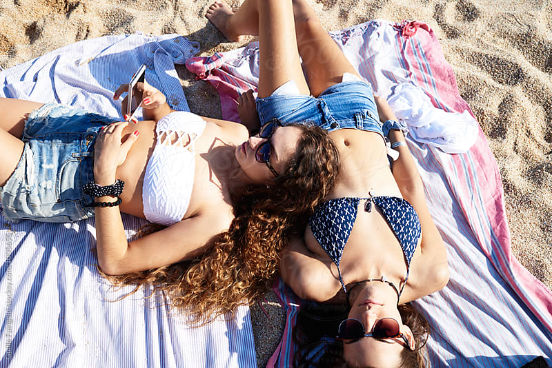 Two girls in sunglasses and shorts sunbathing on beach by Guille Faingold for Stocksy United
