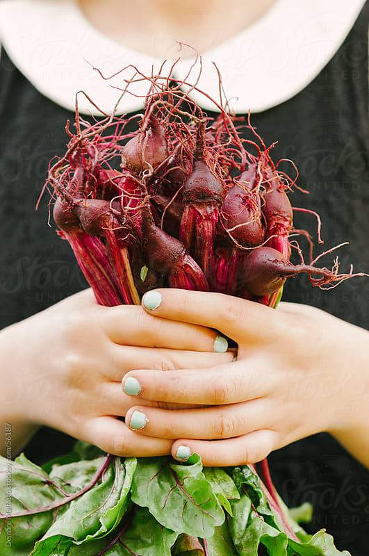 Teenage Girl Holding Beet Roots with Greens by Deirdre Malfatto for Stocksy United